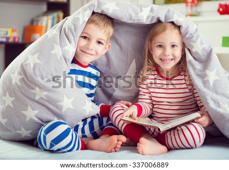 Two happy siblings reading book under the cover - stock photo