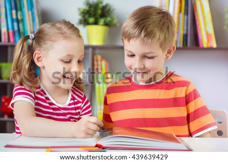 Two happy siblings reading interesting book at desk - stock photo