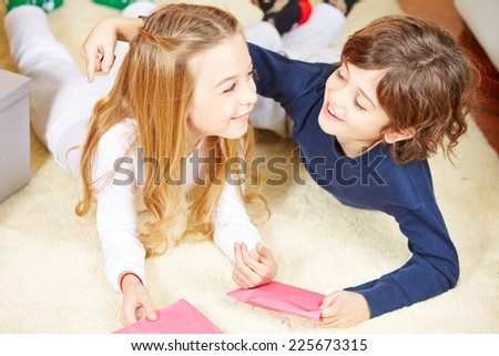 Two happy siblings with greetings cards embracing each other - stock photo