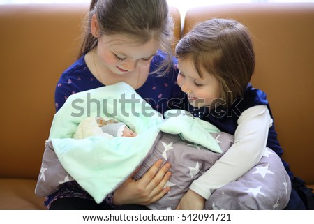 Two happy sisters hold together newborn in blanket on sofa in room