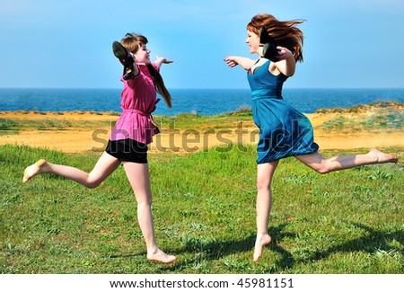 two happy sisters rushing towards each other - stock photo