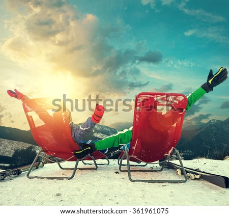 Two happy skiers sitting in chaise-longues on the top of snow mountain - stock photo