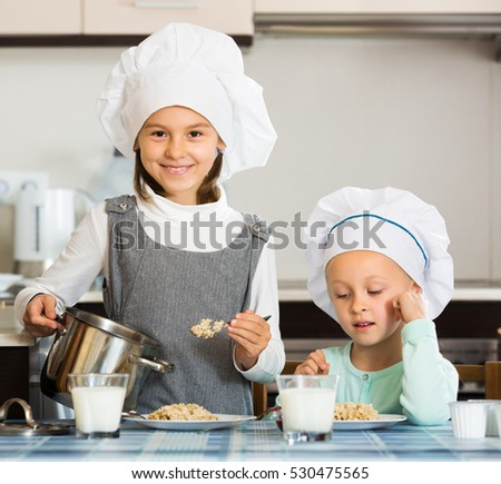 Two happy small girls eating healthy oatmeal in domestic kitchen