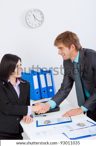 Two happy smile businesspeople or business woman and man client handshaking at office desk, businessman and businesswoman shaking hands with partner in meeting or signing contract, set deal