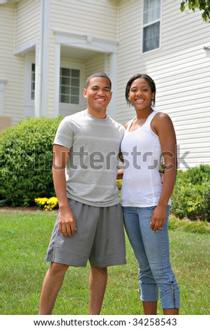Two Happy smiling African American Home Owners in front of House - stock photo