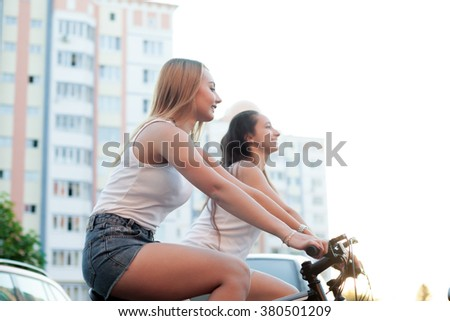 Two happy smiling beautiful blond and brunette young women friends riding bikes in the city in summer beside residential buildings - stock photo