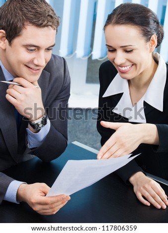 Two happy smiling cheerful young businesspeople working with documents at office - stock photo