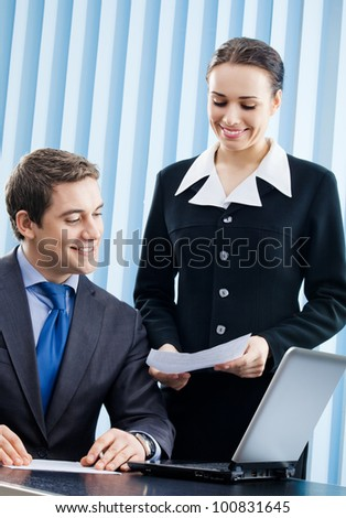 Two happy smiling cheerful young businesspeople working with laptop at office - stock photo