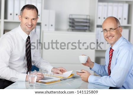 Two happy smiling cheerful young businesspeople working with tablet at office - stock photo