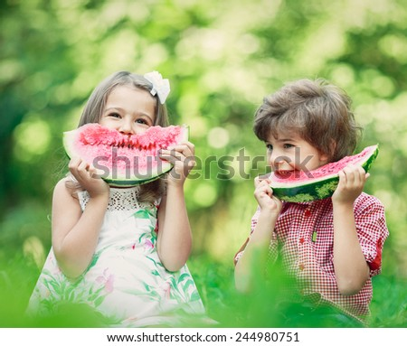 Two happy smiling child eating watermelon in  spring park, sitting on green grass. Picnic concept - stock photo