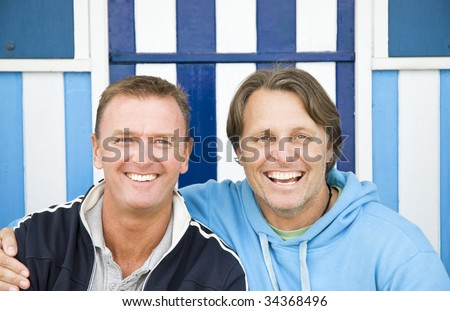 Two happy smiling gay men cuddling. - stock photo