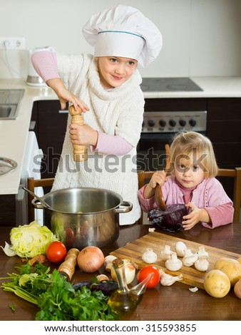 Two happy smiling little sisters with pot at home kitchen