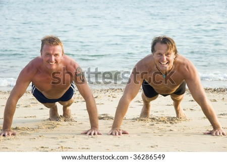 Two happy smiling mature men are performing push ups on a sandy beach. - stock photo