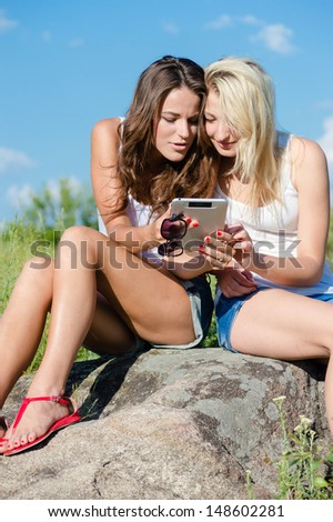 Two happy smiling teen girls looking on tablet pc while sitting on green lawn on summer day