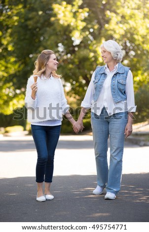 Two happy smiling woman having a slow walk.