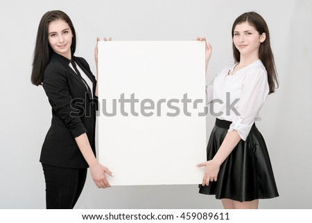 Two happy smiling young business women carrying big blank signboard and showing open palms for product or text - stock photo