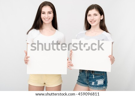 Two happy smiling young business women in casual clothes showing blank signboards on light grey background - stock photo