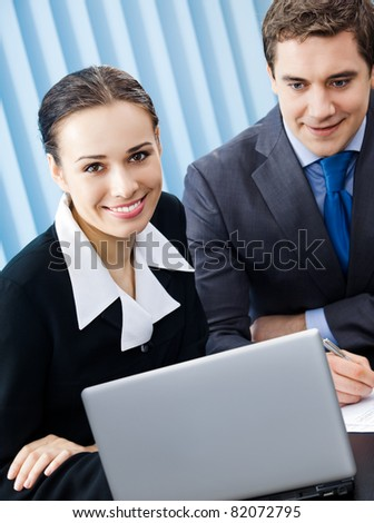 Two happy smiling young businesspeople working with laptop at office