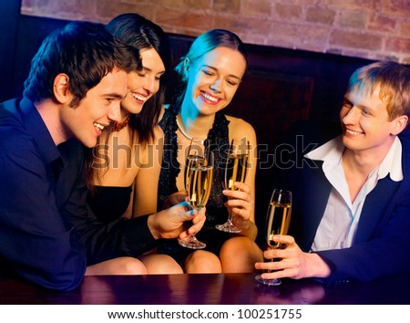 Two happy smiling young couples with champagne at celebration, party or romantic date at club - stock photo