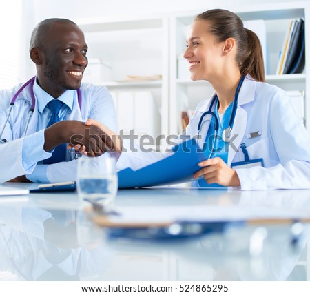 Two happy smiling young medical people handshaking at office