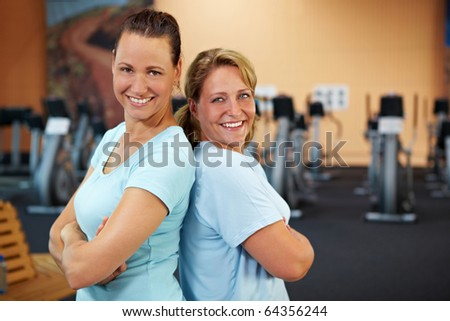 Two happy sporty women standing in a gym