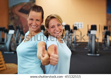 Two happy sporty women standing in a gym and holding their thumbs up - stock photo