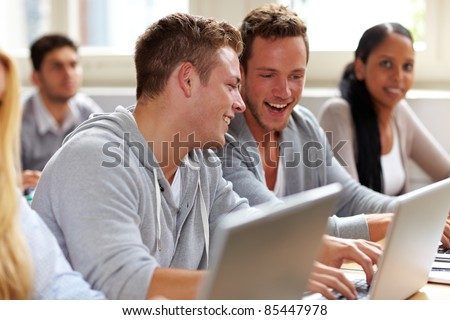Two happy students chatting in university class - stock photo