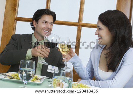 Two happy successful business people toasting glasses at dining table