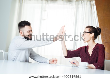 Two happy successful young businesspeople sitting and giving high five on the meeting - stock photo