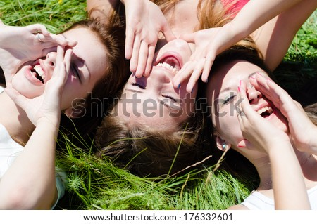 Two happy teen girls lying on green grass looking into sky and holding hands - stock photo