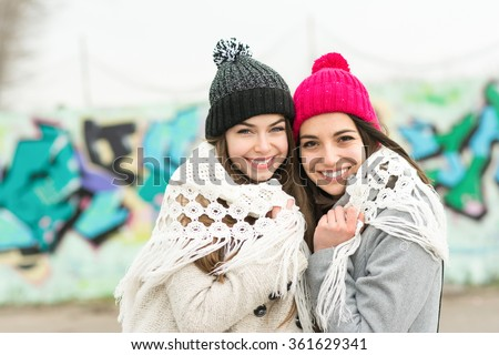 Two happy teenage girls with beanies and shawl in winter smiling and hugging standing in front of colorful graffiti wall. No retouch, horizontal - stock photo