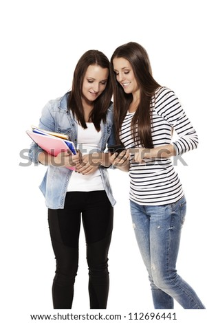 two happy teenage students looking at a smartphone on white background - stock photo