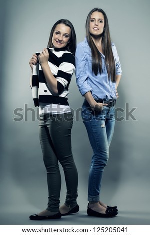 two happy teenagers in front of gray background - stock photo