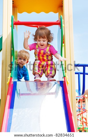 Two happy toddlers ready to slide down - stock photo
