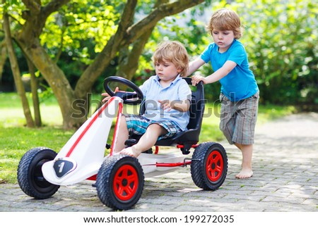 Two happy twin boys driving toy car in summer garden, outdoors. - stock photo