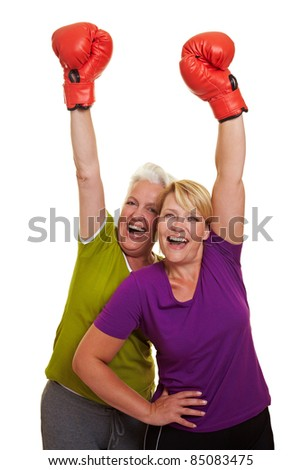 Two happy women cheering with red boxing gloves - stock photo