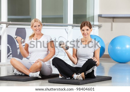 Two happy women doing dumbbell exercises on gym mats in fitness center - stock photo