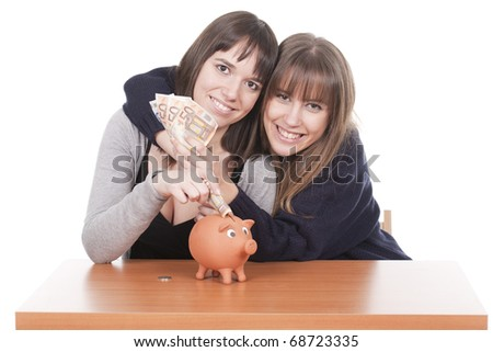 two happy women holding money and putting that in a pig bank - stock photo