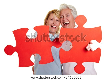 Two happy women holding red jigsaw puzzle pieces - stock photo