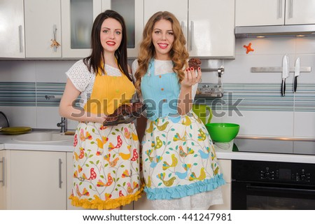 Two happy women in apron at kitchen. - stock photo