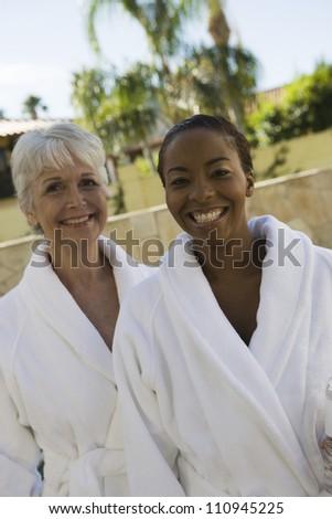 Two happy women in bathrobe - stock photo