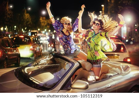 Two happy women in car - stock photo