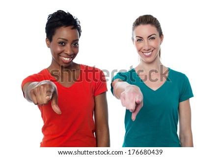 Two happy women in casual clothes and pointing to you