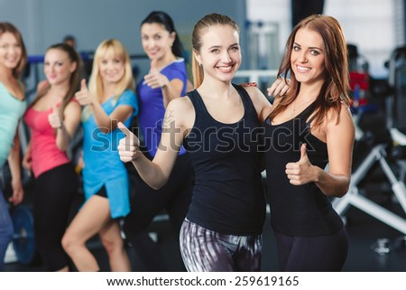 Two happy women in front of group of women in a fitness center holding their thumbs up - stock photo