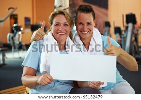 Two happy women in gym holding an empty white billboard - stock photo