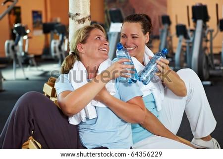 Two happy women in gym taking a break - stock photo