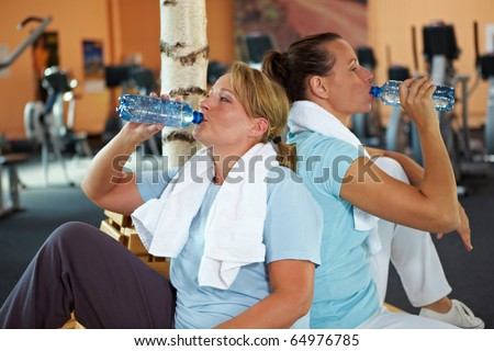 Two happy women in gym taking a break and drinking water - stock photo