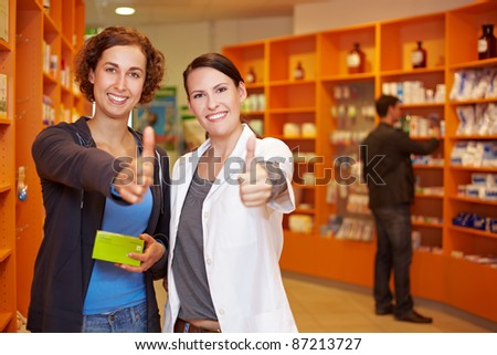 Two happy women in pharmacy holding their thumbs up - stock photo