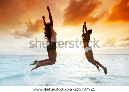 Two happy women jumping on sunset beach near sea