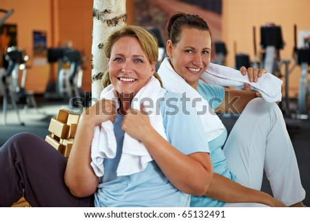 Two happy women relaxing after their fitness training